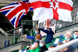 Northern Ireland fans waves flags in the stands before the UEFA Nations League Group 1, League B match at Windsor Park, Belfast. PA Photo. Picture date: Sunday October 11, 2020. 600 fans will be in attendance for the match following UEFA's decision to allow fans to return up to 30 percent of the stadium's capacity in UEFA competitions. See PA story SOCCER N Ireland. Photo credit should read: Liam McBurney/PA Wire. RESTRICTIONS: Editorial use only, No commercial use without prior permission.