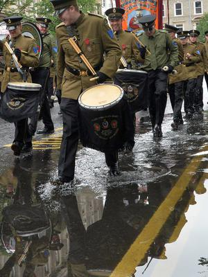 PACEMAKER BELFAST  13/07/2015 Bands men walk threw a puddle during The 12th of July Parades Belfast City on Monday  to commemorate protestant King William of Orange's victory over Catholic King James II at the Battle of the Boyne in 1690. Photo Colm Lenaghan/Pacemaker Press