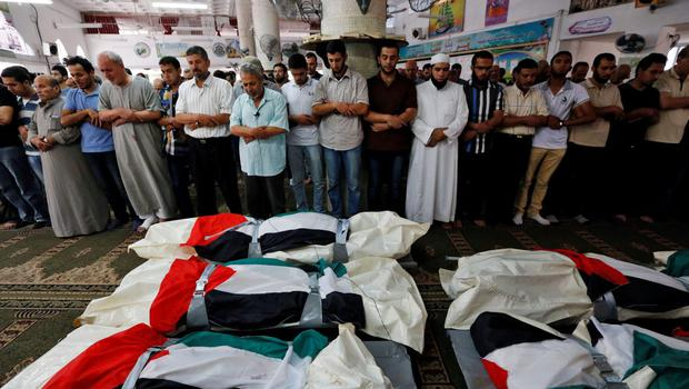 Palestinians pray at a mosque in front of the national flag-draped bodies of five members of the al-Halaq immediate and extended family, killed Sunday by an Israeli strike at their house in Gaza City, during their funeral at a mosque, Monday, July 21, 2014.  (AP Photo/Lefteris Pitarakis)