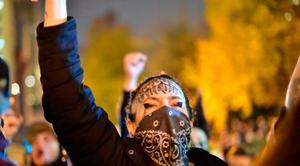 People gather at Portland City Hall to protest of the election of president-elect, Donald Trump, Friday, Nov. 11, 2016, in Portland, Ore. Hundreds of protesters traveled through downtown Portland streets Friday night while others converged at an intersection, not budging as police told them the activity amounted to unlawful assembly. (Mark Graves/The Oregonian via AP)