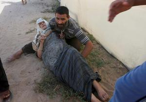 A Palestinian relative helps a wounded woman following an Israeli air strike on a building in Khan Younis in the southern Gaza Strip, Wednesday, July 30, 2014.(AP Photo/Eyad Baba)