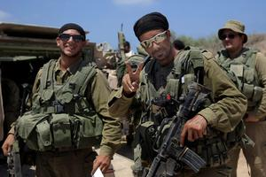 An Israeli reserve soldier gives the victory sign before entering the Gaza Strip near the Israel Gaza border, Tuesday, July 29, 2014.  (AP Photo/Tsafrir Abayov)