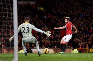 Manchester United's Juan Mata shoots towards Southampton's Fraser Forster during the Barclays Premier League match at Old Trafford, Manchester. Martin Rickett/PA Wire.