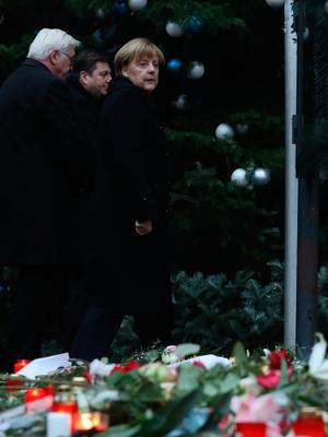BERLIN, GERMANY - DECEMBER 20:  German Chancellor Angela Merkel (R) and Foreign Minister Frank-Walter Steinmeier depart after laying flowers near where yesterday a lorry ploughed through a Christmas market on December 20, 2016 in Berlin, Germany. So far 12 people are confirmed dead and 45 injured. Authorities have confirmed they believe the incident was an attack and have arrested a Pakistani man who they believe was the driver of the truck and who had fled immediately after the attack. Among the dead are a Polish man who was found on the passenger seat of the truck. Police are investigating the possibility that the truck, which belongs to a Polish trucking company, was stolen yesterday morning.  (Photo by Sean Gallup/Getty Images)