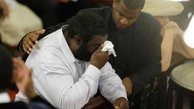 Parishioners pray at the Emanuel A.M.E. Church Sunday, June 21, 2015, in Charleston, S.C., four days after a mass shooting that claimed the lives of it's pastor and eight others. (AP Photo/David Goldman, Pool)