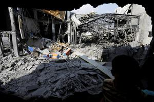 A Palestinian from a neighbouring apartment building inspects the damage of the offices of the Hamas movement's Al-Aqsa satellite TV station, in Gaza City, northern Gaza Strip, destroyed by an Israeli strike, Tuesday, July 29, 2014. (AP Photo/Lefteris Pitarakis)