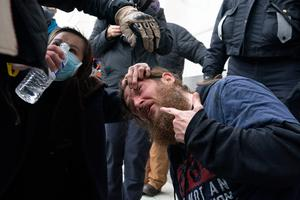 Supporters of President Donald Trump puts water in his eyes after U.S. Capitol Police deployed a chemical agent outside of the U.S. Capitol on Wednesday, Jan. 6, 2021, in Washington. (AP Photo/Jose Luis Magana)