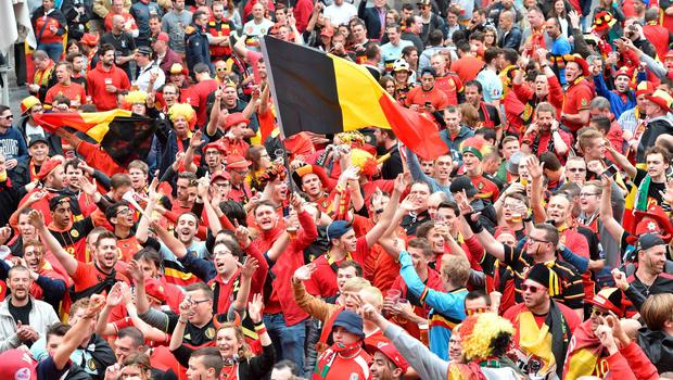 Belgium's supporters wave Belgium's flags as they cheer their team at the main square, La Grand Place, in Lille on July 1, 2016 ahead of the Euro 2016 football tournament quarter final match between Belgium and Wales. / AFP PHOTO / PHILIPPE HUGUENPHILIPPE HUGUEN/AFP/Getty Images