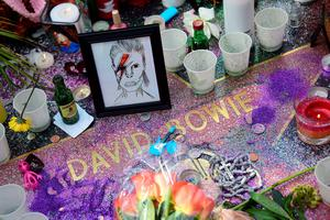 """Flowers and other momentos are left at the Hollywood Star of the late British musician David Bowie in Hollywood, California, on January 11, 2016.  Bowie died at the age of 69 after a secret battle with cancer, prompting a cascade of tributes for one of the most influential and innovative artists of his time. A notoriously private person, Bowie's death was a shock with his death coming just two days after he released his 25th studio album """"Blackstar"""", on his 69th birthday on January 8. """"David Bowie died peacefully today (Sunday) surrounded by his family after a courageous 18-month battle with cancer,"""" said a statement posted January 11 on his official social media accounts.  AFP PHOTO/FREDERIC J. BROWNFREDERIC J. BROWN/AFP/Getty Images"""
