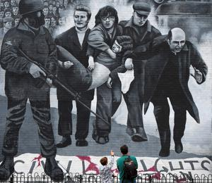 LONDONDERRY, NORTHERN IRELAND - AUGUST 11: A young boy points at a mural depicting a scene from Bloody Sunday as final preparations for the funeral of the late retired Bishop of Derry, Dr. Edward Daly as he lies in state at St. Eugene's Cathedral on August 11, 2016 in Londonderry, Northern Ireland. The iconic image of the then Fr Daly waving a hankerchief over one of the Bloody Sunday victims became one of the most enduring images of the Troubles in Northern Ireland. Bishop Daly who has been described as a fearless peace-builder passed away at the age of 82 following a brief illness, he will be buried this afternoon in the grounds of the cathedral following requiem mass. (Photo by Charles McQuillan/Getty Images)