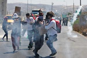 Palestinian protesters against the Israeli military action in Gaza run from tear gas shot by Israeli soldiers, during a demonstration at Hawara checkpoint near the West Bank city of Nablus on Thursday, July 24, 2014. (AP Photo/Nasser Ishtayeh)
