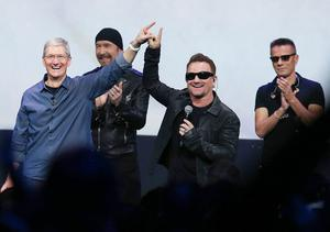 Apple CEO Tim Cook (left) greets the crowd with U2 singer Bono as The Edge and Larry Mullen Jr look on during an Apple special event in Cupertino, California (Photo by Justin Sullivan/Getty Images)