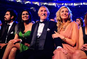 Sir Bruce Forsyth (centre) and his wife Wilnelia (left) sitting with Tess Daly as he wins a Special Recognition award, at the 2011 National Television Awards at the O2 Arena, London. Ian West/PA Wire