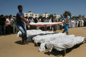 Palestinians prepare the bodies to pray over white coffin-draped bodies of ten members of the Al Astal immediate and extended family, killed by an Israeli strike early at their houses, during their funeral in Khan Younis, in the southern Gaza Strip, Wednesday, July 30, 2014.  (AP Photo/Eyad Baba)