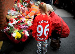People leave tributes outside Anfield stadium before a memorial service to mark the 27th anniversary of the Hillsborough disaster, on April 15, 2016 in Liverpool, England. (Photo by Christopher Furlong/Getty Images)