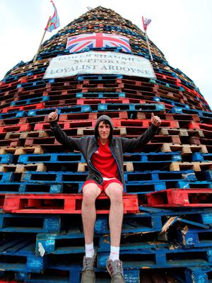 A man sits on  a bonfire on the lower Shankill area of Belfast. AFP PHOTO / PAUL FAITHPAUL FAITH/AFP/Getty Images.