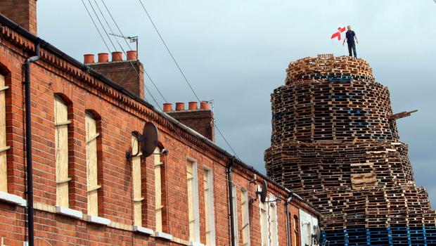 A man stands on top of the bonfire as houses are evacuated and protected at Chobham Street in east Belfast. AFP PHOTO/PAUL FAITHPAUL FAITH/AFP/Getty Images.