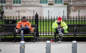 Two workers outside Belfast City Hall at lunch time yesterday