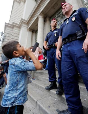 A young migrant boy plays a harmonica to police officers in front of the railway station in Budapest, Hungary, Thursday, Sept. 3, 2015. Over 150,000 migrants have reached Hungary this year, most coming through the southern border with Serbia, and many apply for asylum but quickly try to leave for richer EU countries.(AP Photo/Frank Augstein)