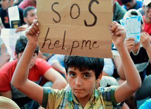 TOPSHOTS Migrant boy holds a sign reading 'SOS help me' as he sits with other migrants in front of the Keleti (East) railway station in Budapest on September 2, 2015. Hungarian authorities face mounting anger from thousands of migrants who are unable to board trains to western European countries after the main Budapest station was closed.  AFP PHOTO / ATTILA KISBENEDEKATTILA KISBENEDEK/AFP/Getty Images