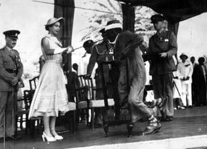 The Queen bestowing a knighthood on Seiyid Bubakr Bin Sheikh Al Kaf, Councillor of the Kathiri State in Eastern Aden, at an open-air investiture in 1954 (PA)
