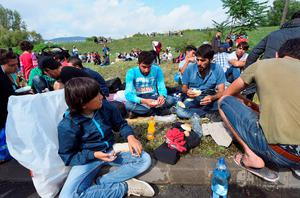 A migrant group sits on the pavment next to the main road near Budaors, Hungary on September 5, 2015 to afterwards head to the Hungarian-Austrian border. Several thousand refugees were transported by 104 Hungarian public buses and coaches to the Austrian border from the Hungarian capital early morning. Migrants from several countries left Hungarian refugee camps in the direction of Austria in the hope to reach Germany.  AFP PHOTO / ATTILA KISBENEDEKATTILA KISBENEDEK/AFP/Getty Images