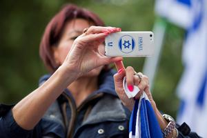A pro-Israeli demonstrators takes a photograph on her mobile phone during a rally outside the gates of Downing Street in London on September 9, 2015. Over 100 pro-Israeli demonstrators and hundreds of pro-Palestinian activists rallied in front of Downing Street in London ahead of a planned visit of Israeli Prime Minister Benjamin Netanyahu. Netanyahu visits Britain this week for talks with his counterpart David Cameron as the right-wing Israeli leader faces diplomatic pressure over West Bank settlements and stalled peace efforts. AFP PHOTO / JUSTIN TALLISJUSTIN TALLIS/AFP/Getty Images