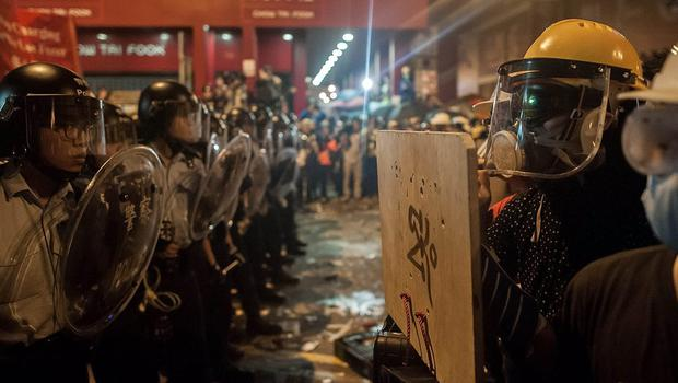 Pro-democracy protesters (R) hold wooden shields during a standoff with police (L) at Mongkok district on November 26, 2014 in Hong Kong. The Mongkok protest site is scheduled for clearance by bailiffs this week after Hong Kong's high court authorised police to arrest protesters who obstruct bailiffs on the three interim restraining orders.  (Photo by Anthony Kwan/Getty Images)