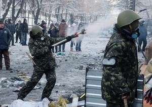A protester aims fireworks at police during clashes, in central Kiev, Ukraine, Thursday, Jan. 23, 2014. Thick black smoke from burning tires engulfed parts of downtown Kiev as an ultimatum issued by the opposition to the president to call early elections or face street rage was set to expire with no sign of a compromise on Thursday. (AP Photo/Efrem Lukatsky)