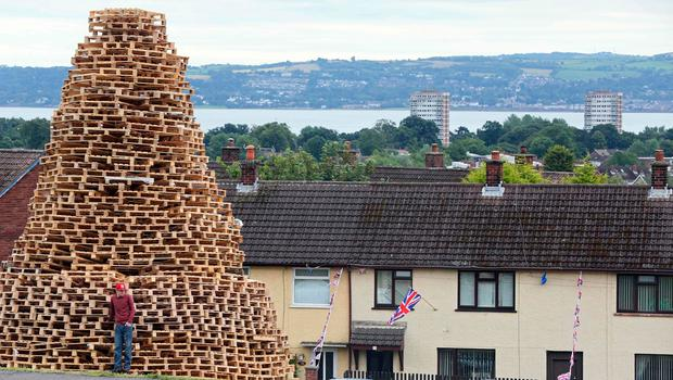 Bonfire builder Ryan Preston poses for a photograph on the Doonbeg bonfire in Rathcoole in north Belfast on July 10, 2017 ahead of the traditional 11th night bonfires. [Photo: Paul Faith/AFP/Getty Images]