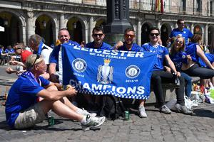 Leicester City's supporters pose with team flag on Plaza Mayor before the UEFA Champions League quarter final first leg football match Club Atletico de Madrid vs Leicester City, in Madrid on April 12, 2017. / AFP PHOTO / CURTO DE LA TORRECURTO DE LA TORRE/AFP/Getty Images