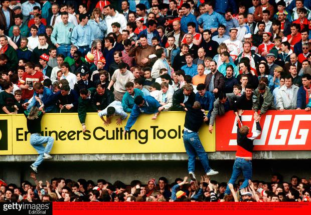 Liverpool fans are pulled to safety on to the upper tier, from the crush that was happening below Credit: Bob Thomas/Getty Images
