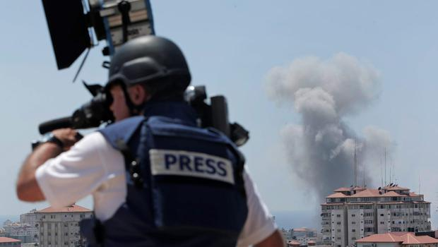 A news cameraman films at a live position as in the background smoke rises from an Israeli strike in Gaza City, Sunday, July 27, 2014. (AP Photo/Lefteris Pitarakis)