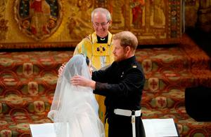 Britain's Prince Harry, Duke of Sussex (R) removes the veil of US actress Meghan Markle (L) as they stand at the altar together before Archbishop of Canterbury Justin Welby (C) in St George's Chapel, Windsor Castle, in Windsor, on May 19, 2018 during their wedding ceremony. / AFP PHOTO / POOL / Owen HumphreysOWEN HUMPHREYS/AFP/Getty Images