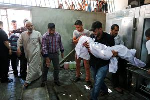 A Palestinian mourner carries the body of Ibrahim Ramadan Abu Daga, 10, killed while in a vehicle hit by a Israeli missile strike in Khan Younis, southern Gaza Strip on Wednesday, July 16, 2014. Hundreds of Palestinian families, their children crying, fled Wednesday, as Israel intensified airstrikes on Hamas targets, including homes of the movement's leaders, following failed Egyptian cease-fire efforts. Before the renewed bombardment, Israel had told tens of thousands of residents of border areas to evacuate their neighborhoods. (AP Photo/Lefteris Pitarakis)