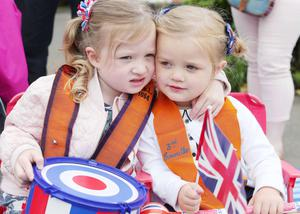 Press Eye - Belfast -  Northern Ireland - 13th July  2015  Belfast's Orange Order annual 12th of July demonstration makes its way through the City Centre to the field at Malone House beside Shaws Bridge.  Left to right.  Elle Knowles(4) with her cousin Phoebe(2) watch the parade on Balmoral Avenue.   Picture by Jonathan Porter/Press Eye
