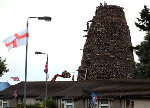 "Men construct a bonfire in the Ballymacash area of Lisburn, as building continues on huge loyalist bonfires, which are traditionally lit on the ""Eleventh night"" to usher in the Twelfth commemorations. PRESS ASSOCIATION Photo. Picture date: Sunday July 10, 2016. Authorities in Northern Ireland are cautiously optimistic the main fixture in the loyal order parading season can pass off peacefully, but have a major policing operation planned to deal with any unrest. See PA story ULSTER Twelfth. Photo credit should read: Brian Lawless/PA Wire"