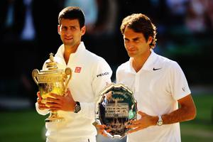 LONDON, ENGLAND - JULY 06:  Novak Djokovic of Serbia poses with the Gentlemen's Singles Trophy next to Roger Federer of Switzerland following his victory in the Gentlemen's Singles Final match on day thirteen of the Wimbledon Lawn Tennis Championships at the All England Lawn Tennis and Croquet Club on July 6, 2014 in London, England.  (Photo by Al Bello/Getty Images