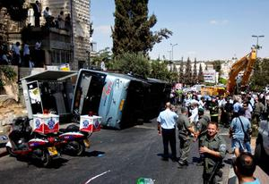 Israelis stand near a flipped bus at the scene of an attack in Jerusalem, Monday, Aug. 4, 2014.  (AP Photo/Sebastian Scheiner)