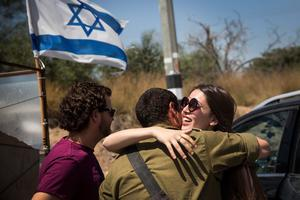 An Israeli soldier meets with his loved ones during a 12-hour ceasefire just outside the militarised zone near the Israeli-Gaza border on July 26, 2014 near Zikim, Israel.  (Photo by Andrew Burton/Getty Images)