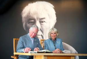The Prince of Wales signs the visitors book while the Duchess of Cornwall looks on during a tour of the new centre in Bellaghy, dedicated to Seamus Heaney during their visit to Northern Ireland.  Liam McBurney/PA Wire