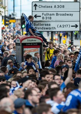 A young Chelsea fan sits on a phone box during a parade to celebrate Chelsea winning the Barclays Premier League, in London. PRESS ASSOCIATION Photo. Picture date: Monday May 25, 2015. See PA story SOCCER Chelsea. Photo credit should read: Daniel Hambury/PA Wire.