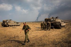 "SDEROT, ISRAEL - JULY 22:  Israeli soldiers stand near their tank while smoke due to airstrikes and shelling rises from Gaza on July 22, 2014 near Sderot, Israel. As operation ""Protective Edge"" goes into it's third week, the death toll continues to mount, including 27 Israeli soldiers and over 500 people in Gaza, the vast majority of whom are civilians.  (Photo by Andrew Burton/Getty Images)"