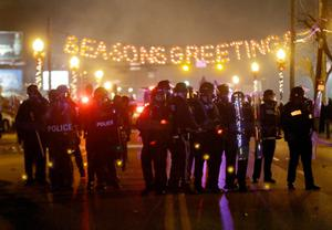 Police gather on the street as protesters react after the announcement of the grand jury decision Monday, Nov. 24, 2014, in Ferguson, Mo. A grand jury has decided not to indict Ferguson police officer Darren Wilson in the death of Michael Brown, the unarmed, black 18-year-old whose fatal shooting sparked sometimes violent protests. (AP Photo/Charlie Riedel)
