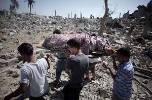 Palestinians carry a lifeless body found under the rubble while people inspect the damage caused by Israeli strikes in the village of Khuzaa, southern Gaza Strip, close to the Israeli border, Friday, Aug. 1, 2014 (AP Photo/Khalil Hamra)