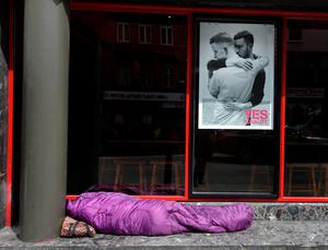 A homeless person lays beneath a billboard poster promoting the Yes campaign in favour of same-sex marriage on May 22, 2015 in Dublin, Ireland.  (Photo by Charles McQuillan/Getty Images)