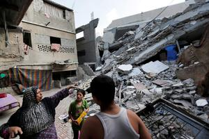 Palestinian Heygar Jendiyah, left, points to where the family house kitchen once stood, partially destroyed by an Israeli strike earlier during the war, as her children Ranin, 10, center, and Helmi, right, listen, in the Sabra neighborhood of Gaza City, northern Gaza Strip, Thursday, July 31, 2014. (AP Photo/Lefteris Pitarakis)