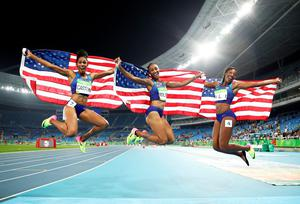 RIO DE JANEIRO, BRAZIL - AUGUST 17:  (L-R) Bronze medalist Kristi Castlin, gold medalist Brianna Rollins and silver medalist Nia Ali of the United States celebrate with American flags after the Women's 100m Hurdles Final on Day 12 of the Rio 2016 Olympic Games at the Olympic Stadium on August 17, 2016 in Rio de Janeiro, Brazil.  (Photo by Cameron Spencer/Getty Images) *** BESTPIX ***