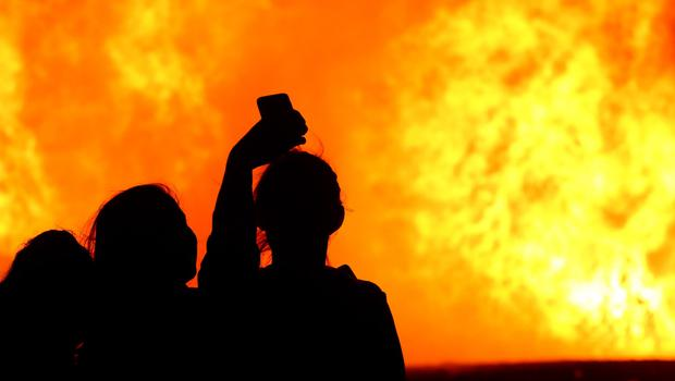 A group of women take a selfie as the Ballymacash bonfire burns in Lisburn. William Cherry/Presseye.