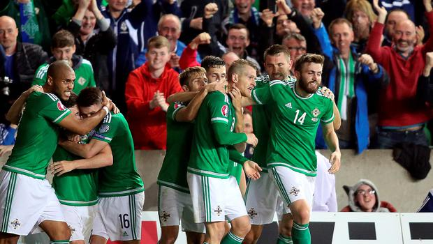 Northern Ireland's midfielder Steven Davis (C) celebrates with teammates after scoring the opening goal during the UEFA Euro 2016 qualifying Group F football match between Northern Ireland and Greece at Windsor Park in Belfast, Northern Ireland, on October 8, 2015. AFP PHOTO / PAUL FAITHPAUL FAITH/AFP/Getty Images
